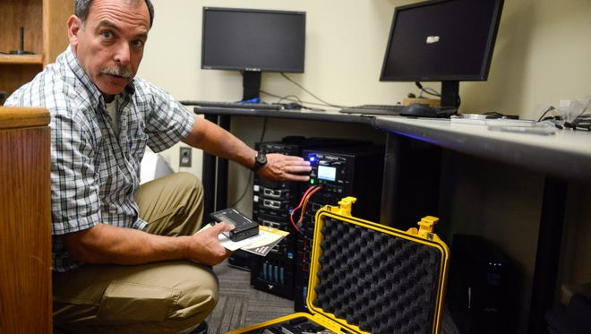 ADVANCE FOR USE SATURDAY, SEPT. 9 - In this Sept. 1, 2017 photo, Mike Gurzi, a digital forensic analyst in the Computer Crime Unit of the Bozeman, Mont., Police Department, explains the process of removing information from devices, such as computers or cell phones, in a way that prevents the information from being altered. Once acquired, Gurzi then can analyze the data, write a report and store the information. (Rachel Leathe/Bozeman Daily Chronicle via AP)