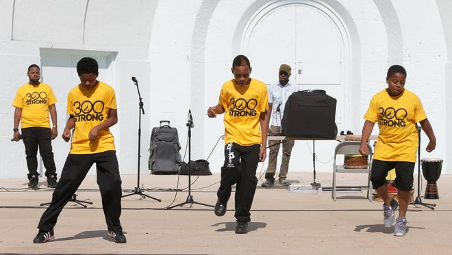"""Members of the Running Rebels perform with music, poetry and dance during the Black Male Collaborative """"300 Strong Rally"""" at the Washington Park Bandshell on Sept. 26, 2015."""
