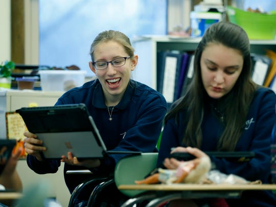 Though home-schooled, 11th grader Christen Ketchum attends a precalculus class at Mercy High School, seen here looking at her laptop and sitting behind also 11th grader Karis Kalley. Mercy has accepted home-schooled students in part-time classes, which is new in the area for the big private schools.