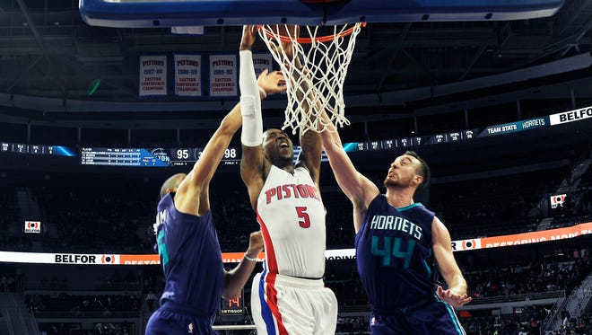 Pistons' Kentavious Caldwell-Pope dunks over the Hornets' Nicolas Batum, left, and Frank Kaminsky in the fourth quarter.Pope had 33 points and 9 rebounds.