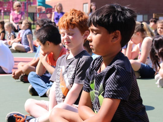 Kindergartners Jackson Plager (left) and Devin Dave are eager and willing participants in an outdoor mindfulness session at Woodland Schoon on May 17.