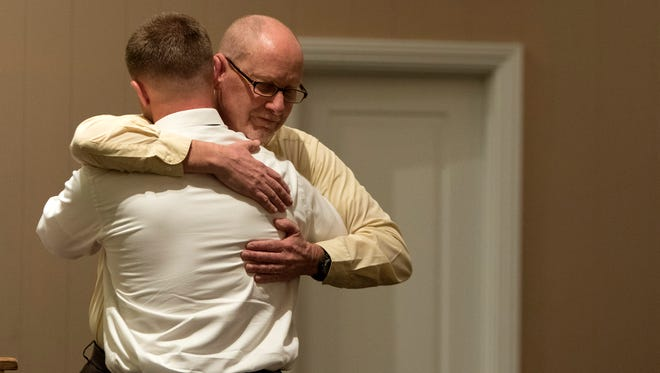 Brett Wuest, left, receives a hug from Dan Patterson during the Ventura County Rescue Mission's Life Recovery Program graduation ceremony Tuesday at Faith Community Church in Oxnard.