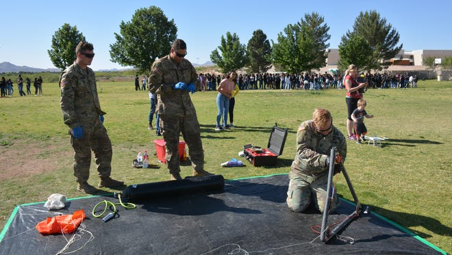 Lt. Jordan Henrickson, 1st Brigade, 1st Armored Div., works on the payload for the weather balloon launch at SantaTeresa Middle School. He is assisted by Spec. Zack Harrison and Spec. Devin Layman.