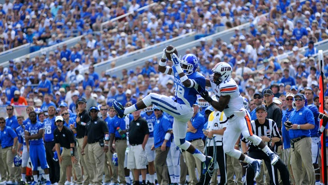 UK's Garrett Johnson grabs a 13-yard pass from Patrick Towles, over UT Martin's Tanio Fears-Perez, Saturday, Aug. 30, 2014 at Commonwealth Stadium in Lexington. Photo by Tim Webb, Special to the CJ