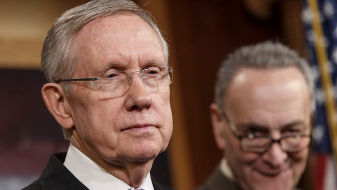 Senate Minority Leader Harry Reid, D-Nev., left, accompanied by Sen. Chuck Schumer, D-N.Y., listens during a news conference on Capitol Hill.