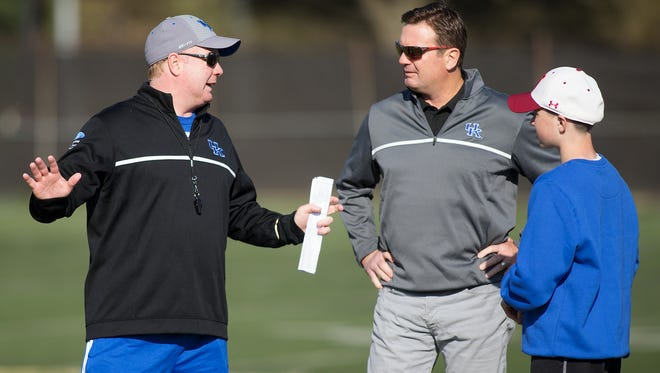 UK head football coach Mark Stoops, left, talks with his brother Bob Stoops, center, during football practice, Wednesday, April 23, 2014 at Nutter Training Facility in Lexington. Photo by Jonathan Palmer, Special to the CJ