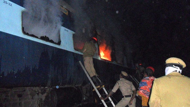 Indian rescue personnel attempt to open a window of a burning carriage of the Nanded-Bangalore Express near Puttapartihi on Dec. 28, 2013, after a fire engulfed the train.