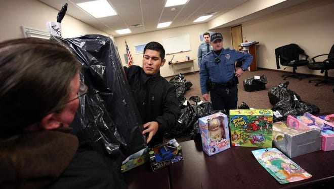 Alex Bravo (second from left), a cadet in Ocean County Sheriff's Explorers Post 1, helps distribute toys to needy families in Ocean County last Christmas.