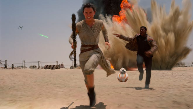 """This photo provided by Disney shows Daisey Ridley as Rey, left, and John Boyega as Finn, in a scene from the new film, """"Star Wars: The Force Awakens,"""" directed by J.J. Abrams. Film Frame)"""