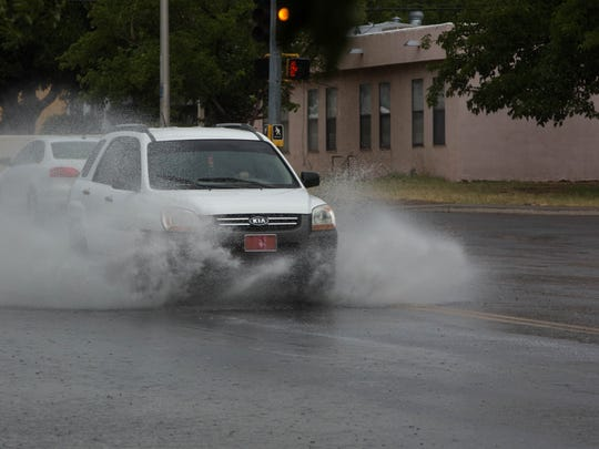 Vehicles driving through the Locust and Missouri Ave intersection, where excess water was collecting during the thunderstorm that the National Weather Service sent out an advisory about, Wednesday July 19, 2017.