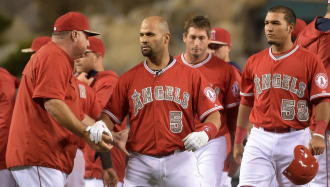 Angels first baseman Albert Pujols celebrates with manager Mike Scioscia and teammates after a walk-off single.