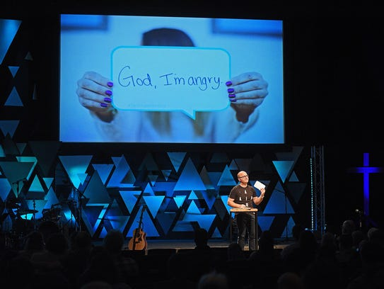 Adam Weber, lead pastor at Embrace Church, holds up