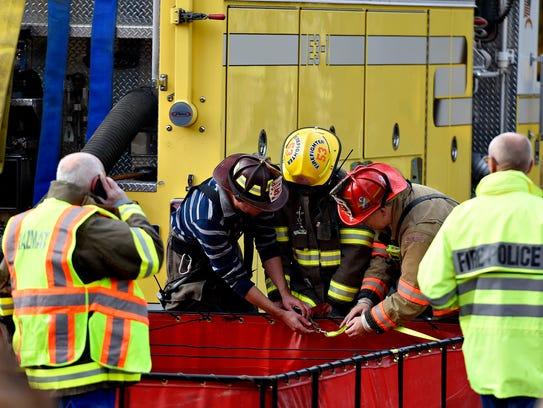 Fire crews and hazmat response team work to contain