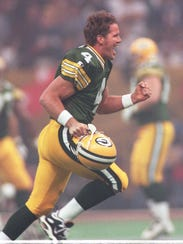 Brett Favre sprints off the field after throwing a touchdown pass to Antonio Freeman in the second quarter.