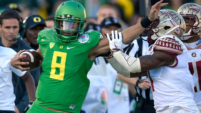 Oregon quarterback Marcus Mariota, left, pushes away Florida State safety Tyler Hunter during the first half of the Rose Bowl NCAA college football playoff semifinal, Thursday, Jan. 1, 2015, in Pasadena, Calif. (AP Photo/Mark J. Terrill)