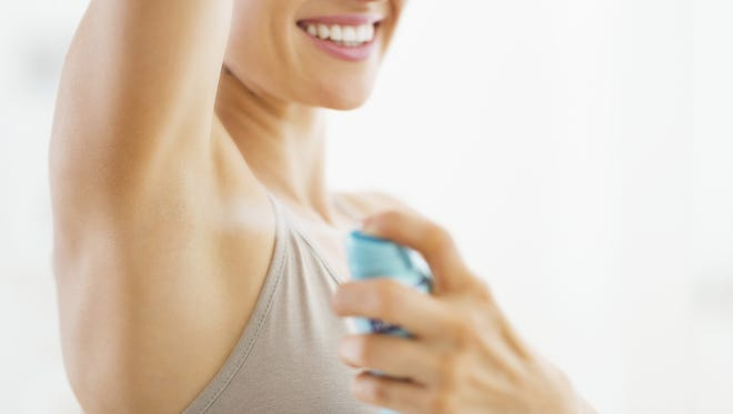 Young woman applying deodorant on underarm. Closeup