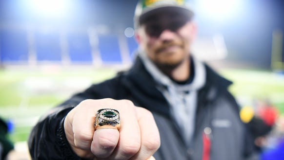 Noah Craig holds out his state championship ring he
