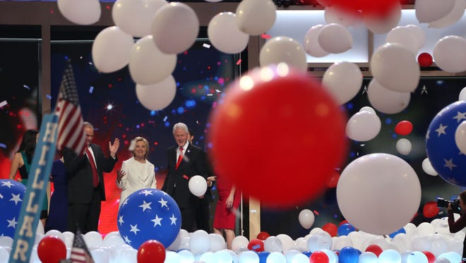 Tim Kaine, Hillary Clinton and Bill Clinton celebrate as balloons drop on the Democratic National Convention stage and floor after Hillary Clinton's acceptance speech Thursday.