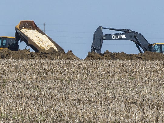 "Dead chickens are buried in a farm field near Rose Acre Farms, Tuesday morning. Rose Acre Farms is depopulating its Winterset egg-laying operation, shown here Tuesday May 12, 2015, just west of Winterset,  after the avian influenza virus was discovered two weeks ago. An estimated 1.5 million birds will be destroyed ""to combat the risk of spreading avian influenza to other locations,"" said Tony Wesner, Rose Acre Farms' chief operating officer."