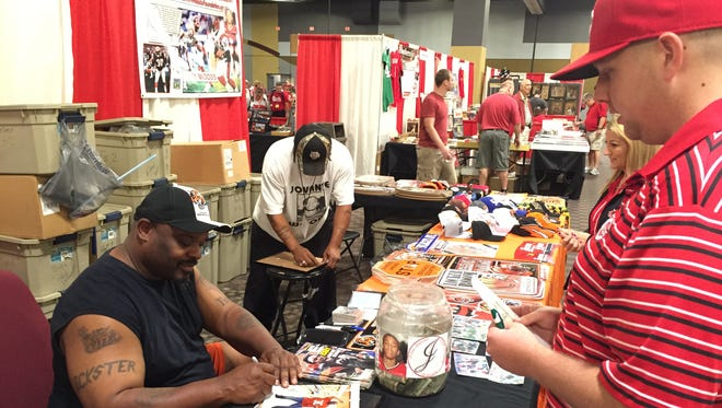 "Former Cincinnati Bengals running back Ickey Woods signs a ""cold cut"" picture for a fan at the Cincy Sports Fest 2015 at the Northern Kentucky Convention Center."