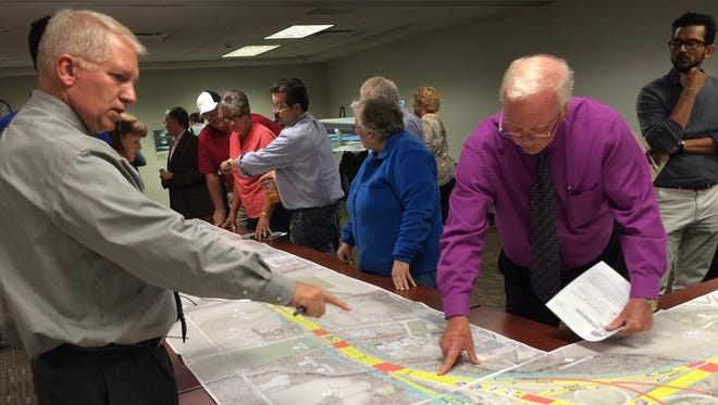Visitors to an Iowa Department of Transportation public information meeting examine plans for a redesigned I-80 and I-380 interchange on Tuesday.