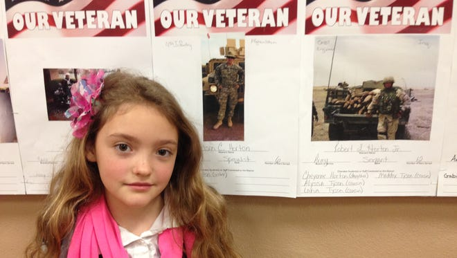 Cherokee Elementary fourth-grader Cheyenne Horton, 9, stands with her two posters representing veterans in her family. Her father served 14 years and her brother currently serves.
