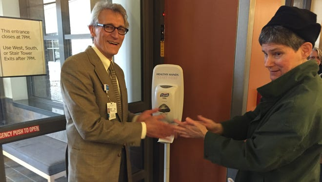 Dr. MIchael Nazar of Rochester Regional Health and reporter Patti Singer  use hand sanitizing gel before shaking hands.