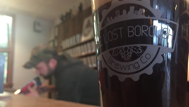 Dan Western, co-founder of the Lost Borough Brewing Company, works in the background on the brewery's bar. Lost Borough celebrates its first anniversary this weekend.