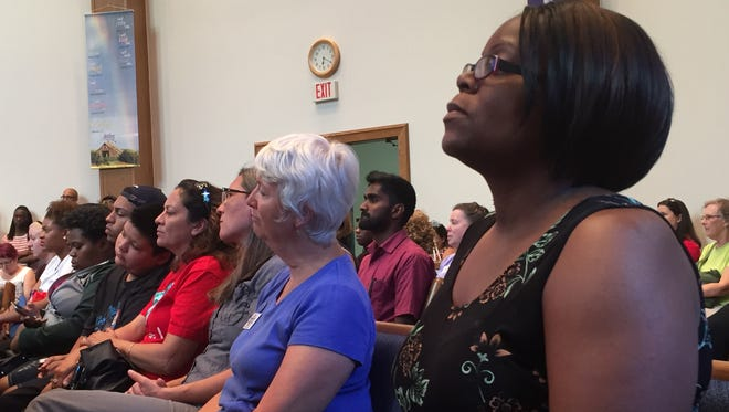 Kim Milton-Mackey (right) and Lynn Bartley listen to a speaker during a Solidarity Rally Friday, July 8, 2016 at Union Missionary Baptist Church.