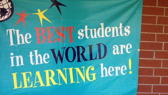 A motivational slogan displayed on wall outside of Bond Elementary School.