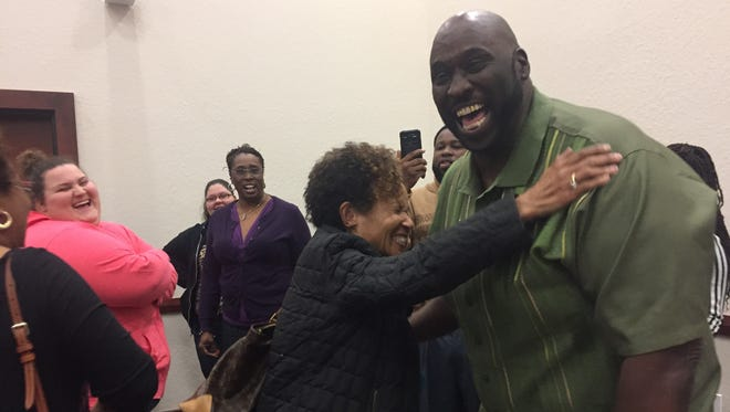Joseph Nathaniel hugs Jacqueline Warrior, Indian River County NAACP education chairwoman, after he's reinstated by the the School Board.
