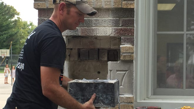 Shawn Edelen maintenance director, removes the time capsule found in the cornerstone at Davis Elementary, Grinnell.