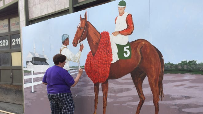 Artist Judy Salton puts the finishing touches on a new mural outside of the Cooperative Gallery on State Street in Binghamton showing Exterminator after his 1918 Kentucky Derby victory.
