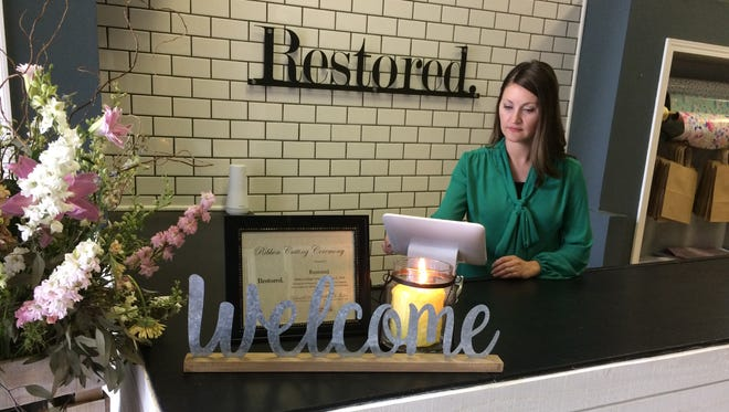 Jessica Cate, a licensed clinical addictions counselor, works behind the counter at Restored, a new retail store and counseling service in the Depot District.
