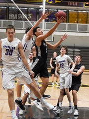 Ankeny Centennial's Hunter Strait (5) goes in for a