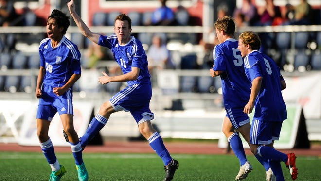 Memorial's Andrew Cross (13) celebrates with teammates after scoring a goal during the Class 2A state championship against Chesterton at Carroll Stadium in Indianapolis, Saturday, Oct. 29, 2016. Memorial beat Chesterton 2-1.