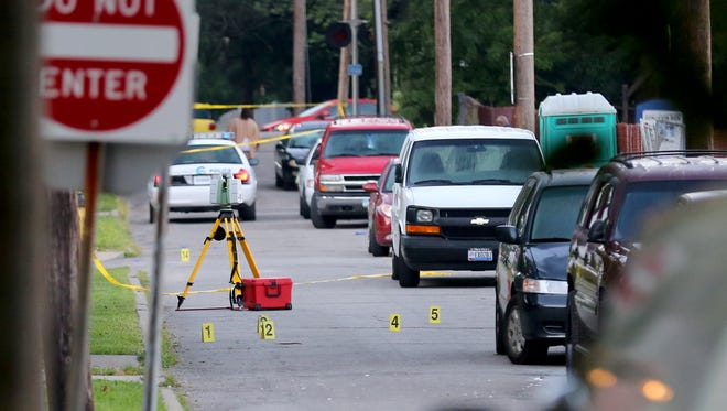Cincinnati police officers investigate the scene on Mathis and Prentice in Madisonville after an overnight shooting.  Multiple  people were shot, two fatally. The bullet markers are near the Elks Home Lodge.