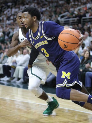 Michigan guard Zavier Simpson drives by Michigan State guard Tum Tum Nairn Jr. in the second half Saturday, Jan. 13, 2018 at the Breslin Center in East Lansing.