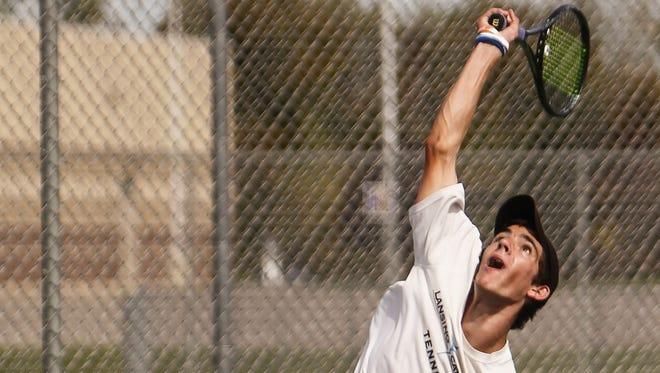 No. 1 singles champion Matt Heeder of Lansing Catholic serves against Williamston freshman Oliver Weaver in their  final match, Thursday, September 25, 2014.