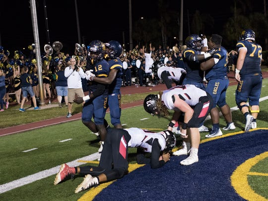 Naples receiver Wooby Theork (12) celebrates with teammates after scoring a winning touchdown in the final seconds of the game against Port Charlotte at Naples High Friday night, November 10, 2017.