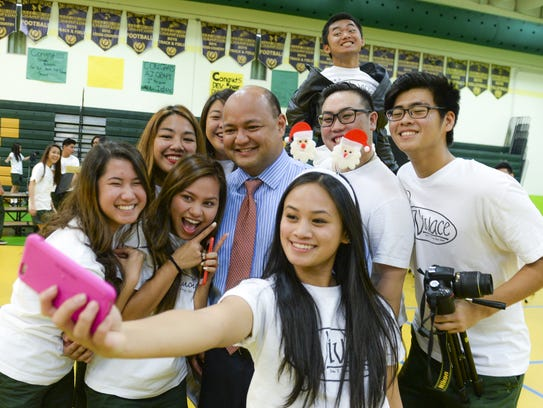 In this Dec. 16, 2016, file photo, Guam Department of Education Superintendent Jon Fernandez poses for a selfie photo with Vivace choir members after John F. Kennedy High's annual Sing for a Cause.