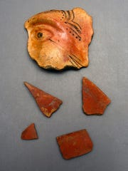 Sherds of Aztec tradition red filmed pottery found at the Luna settlement, two with traces of black painted designs, with a modeled face sherd discovered on the Emanuel Point I wreck, without scale.