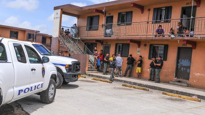 Guam Police Department officers and detectives talk with residents at the Hemlani's Harmon Apartments.