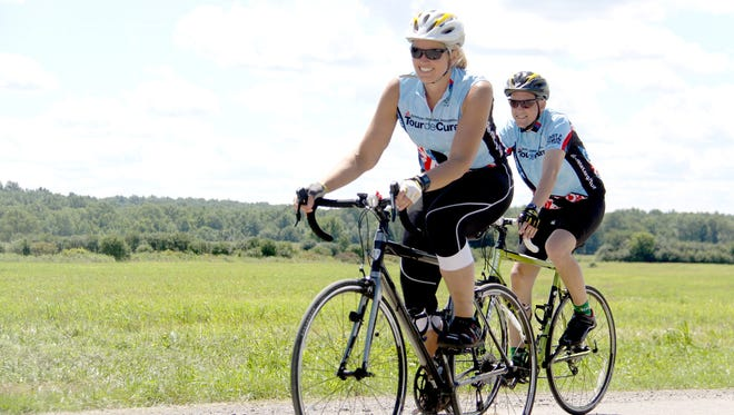 Linda Richards cycles in Geneseo with her husband, Devin Richards.