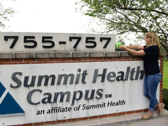 Keila Barrett, president of Chambersburg Lyme Alliance, ties green ribbons around town, including many schools and at Summit Health, Monday, May 9, 2016. May is National Lyme Disease Awareness Month.