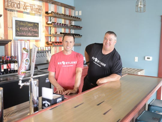 Darin Spindler, left, and Jay Gosser, owners of Heartland Pizza, pose at their bar made of wood from a bowling lane. Aug. 3, 2017.