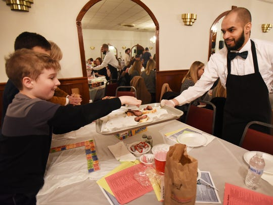 """RJ Cusick, 9, of Rutherford picks a small snack of beef on bread during the first charity event of the Betty & Buddy Ersalesi Scholarship Fund called """"Board Games and Beefsteak"""" at The Elks Club in Rutherford on March 25, 2018."""