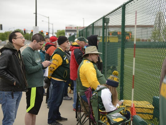 Green Bay Packers fans line the fence along Clarke