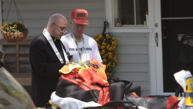 Father Matthew Fernan and John Clear pray near the scene of a fatal explosion in Hastings.