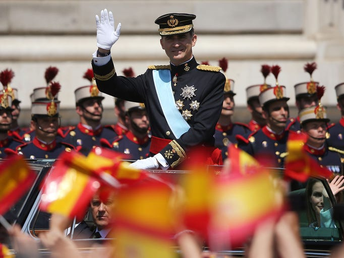 King Felipe VI greets the crowd as he arrives at the Royal Palace during his coronation ceremony June 19 in Madrid. His father, former King Juan Carlos of Spain, abdicated on June 2 after a 39 year reign.